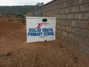 School with new sign in the middle of the bush.