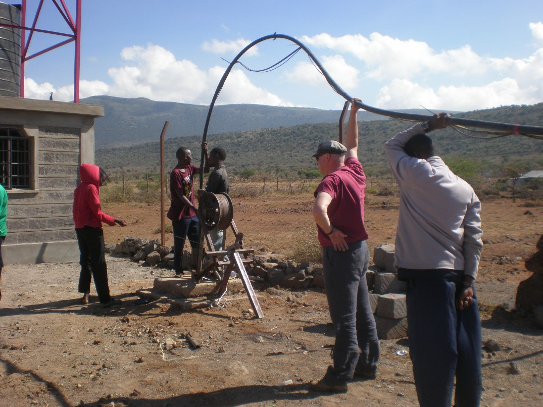 Trying to push the long pipe down the bore-hole.
